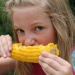 Young Girl Eating Corn — Stock Photo #13494419