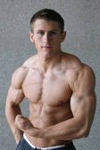 Young muscular man flexing his biceps — Stock Photo