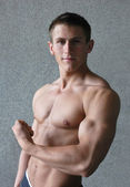 Young muscular man flexing his biceps — Stok fotoğraf