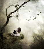 Lonely girl sitting on a rock in sorrow — Stock Photo