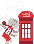 Cat smokes near a telephone booth — Stock Photo