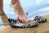 Women's feet resting on a beach — Stock Photo