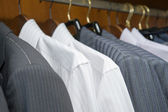 Hangers with jackets and shirts of man's clothing — Stock Photo