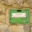 Royalty-Free Stock Photo: Old Green Donations Box Set in Stone Wall.