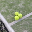 Tennis or paddle balls on synthetic grass of paddle court - Stock Photo