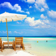 View of nice tropical empty sandy beach with umbrella and beach chair  — Stock Photo