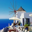 Santorini - view with restaurant and windmill - Stock Photo