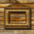 Stock Photo: Antique gilded frame over wooden wall