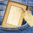 Vintage paper frame with blank tag in jeans pocket - Stockfoto