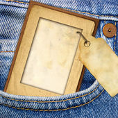 Vintage paper frame with blank tag in jeans pocket — Stock Photo