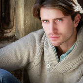 Portrait of young attractive man sitting near window — Stock Photo