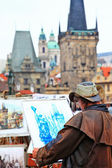 Prague, painter drawing a Charles bridge — Stockfoto