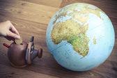 Money box with globe of world — Stock Photo