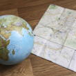 Globe and map on the wooden floor — Zdjęcie stockowe
