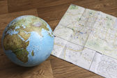 Globe and map on the wooden floor — Stock Photo
