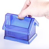 Blue House Money Box with man hand and coin on White Background — Stockfoto