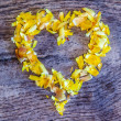 A heart from petals lying on a wooden table — Stock Photo #41445277