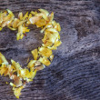 A heart from petals lying on a wooden table — Stock Photo
