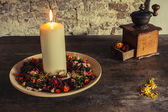 Candle on the wooden plate with coffee mill — Stok fotoğraf