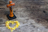 Beautiful old cross with jesus and heart from leafs on the old wooden floor — Stock Photo