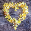 A heart from petals lying on a wooden table — Stock Photo #43255683