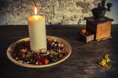 Candle on the wooden plate with coffee mill — Stock Photo