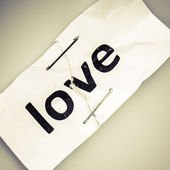 """""""Love"""" word written on torn and stapled paper — Stok fotoğraf"""