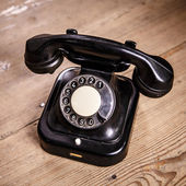 Old black phone with dust and scratches on wooden floor — Stock Photo