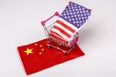 Shopping cart with USA flag on China flag — Stock Photo
