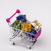 Vánoční dárky v nákupním vozíku, izolované na bílém — Stock fotografie