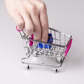 Pink shopping cart in woman hand and blue gift — Stock Photo