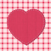 Checkered background with textile heart label — Stock Vector