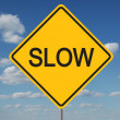 Stock Photo: Slow Traffic Sign with clouds