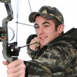 Young hunter with bow aiming - Foto Stock
