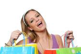 Jong meisje met boodschappentassen tonen opwinding — Stockfoto
