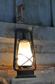 Old vintage lamp hanging from a wooden wall — Stock Photo