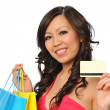 Beautiful asian model posing with shopping bags and credit card — Stock Photo