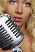Blond singer on microphone — Stock Photo
