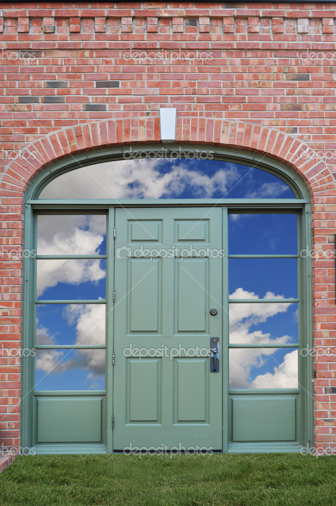Green door with clouds behind and grass as a carpet  Stock Photo #13606750