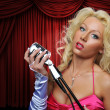 Singer with vintage microphone on stage — Stock Photo