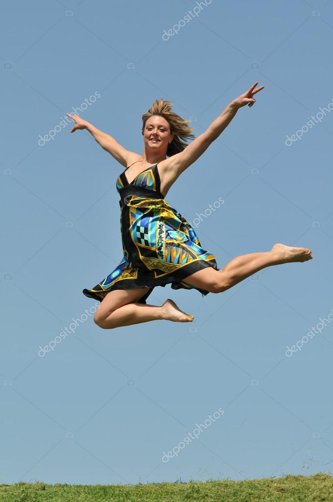 Young woman jumping outdoors agains a blue sky — Stock Photo #13737774