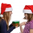 Two girls sharing a Christmas present — Stock Photo #13910622