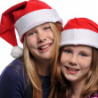 Two girls wearing Christmas hats — Stock Photo