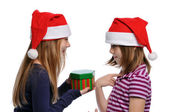 Two girls sharing a Christmas present — Stock Photo
