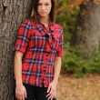 Young Woman standing by a tree — Stock Photo