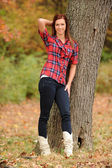 Young Woman standing by a tree — Stock fotografie