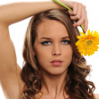 Young Beautiful woman holding a yellow flower — Stock Photo