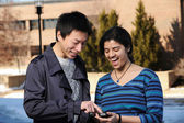 Estudiantes universitarios con teléfono celular — Foto de Stock