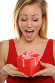 Young Blond Woman Holding a valentine gift and expressing excite — Stock Photo