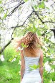 Beautiful blonde girl in spring garden — Stock Photo